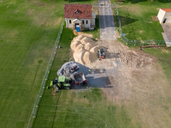Bobcat loading subsoil / subsurface / sports turf drainage sand and aggregate onto a hopper near the old pump house at Langley Park, Perth, Western Australia