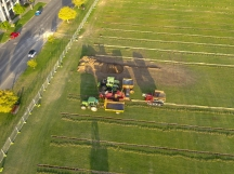 Mastenbroek drainage machine feeding aggregate, sand and draincoil slotted drainage pipe into a precision laser levelled trench. Beautiful sunset photo of the green grass of Langley Park, Perth, taken by Intrepid Drones.