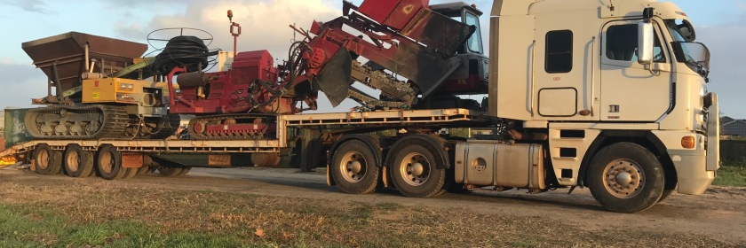 Subsurface Water Management prime mover bringing drainage machinery (hopper, conveyor, chaser bin, Mastenbroek drainage machine) to William Henry Oval, Taylor Private Estate, Caversham, WA for subsurface drainage project logistics.